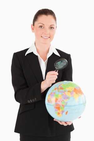 Charming female in suit holding a globe and using a magnifying glass while standing against a white background photo