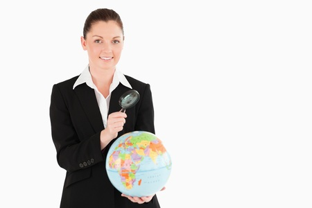 Pretty female in suit holding a globe and using a magnifying glass while standing against a white background Stock Photo - 11179428