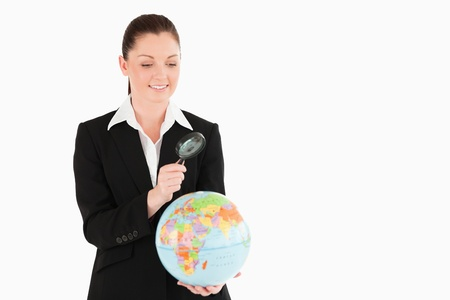Cute female in suit holding a globe and using a magnifying glass while standing against a white background Stock Photo - 11179427