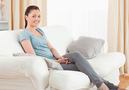 sitting on: Beautiful woman posing while sitting on a sofa in the living room Stock Photo