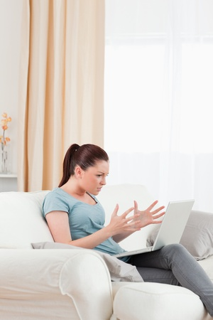 nice looking: Good looking upset woman gambling with her computer while sitting on a sofa in the living room Stock Photo