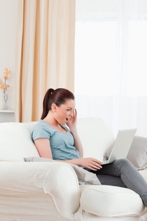 Pretty woman relaxing with her laptop while sitting on a sofa in the living room photo
