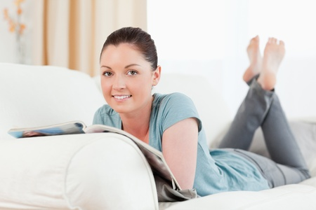Good looking woman reading a magazine while lying on a sofa in the living room photo