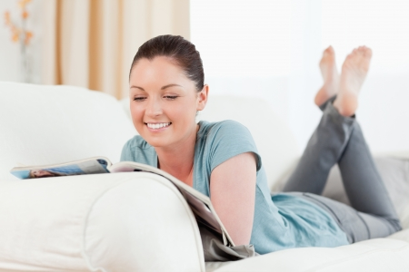 Charming woman reading a magazine while lying on a sofa in the living room photo