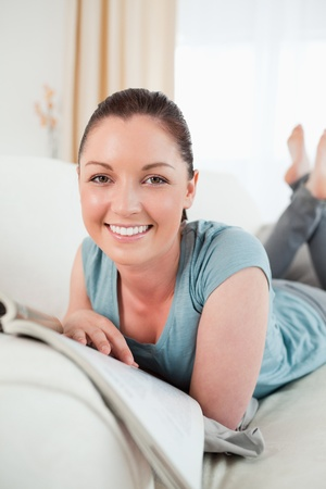 Cute woman reading a magazine while lying on a sofa in the living room photo