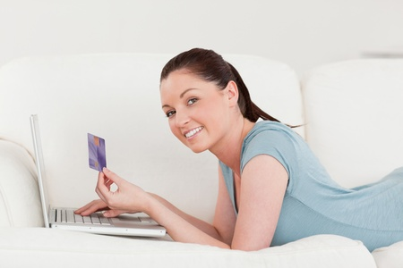 Side view of a beautiful woman making an online payment with her credit card while lying on a sofa in the living room photo