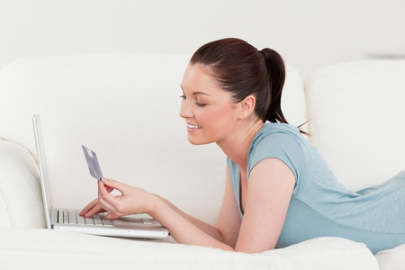 Side view of a good looking woman making an online payment with her credit card while lying on a sofa in the living room photo