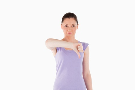 Good looking woman pointing her thumb down while standing against a white background photo