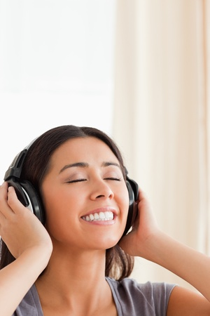close up of  a smiling woman with closed eyes and earphones in livingroom photo