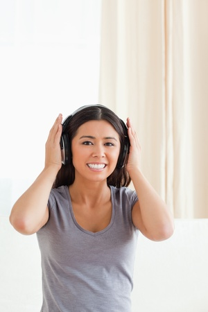 smiling woman with earphones looking into camera in livingroom photo