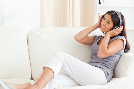 woman with earphones looking up sitting on sofa in livingroom photo