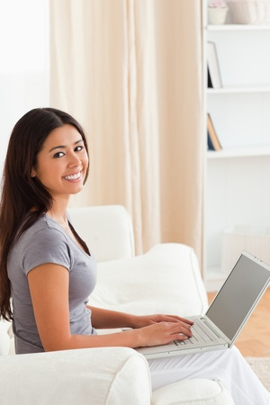smiling woman sitting on sofa with notebook looking into camera in livingroom photo