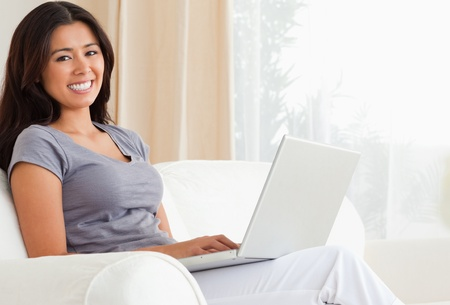 working woman sitting on sofa with notebook looking into camera in livingroom Stock Photo - 11180613