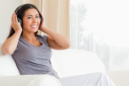 woman sitting on sofa with earphones looking up in livingroom photo