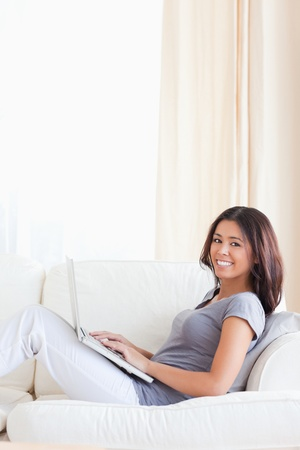 cute woman smiling  into camera while sitting on sofa in livingroom photo