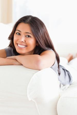 looking into camera: donna sorridente sdraiata sul divano con le braccia incrociate guardando la telecamera in soggiorno