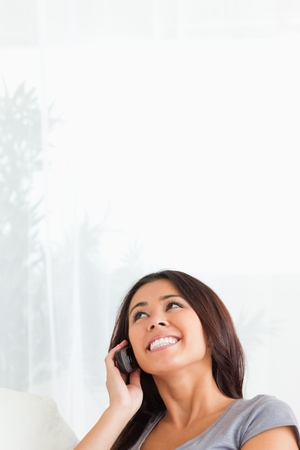 charming woman with mobile looking at the ceiling in livingroom Stock Photo - 11180581