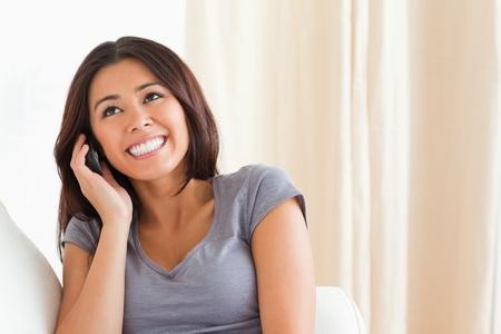 home phone: cheerful woman phoning in livingroom Stock Photo