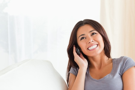 dark-haired woman phoning in livingroom photo