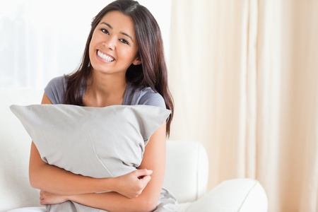 smiling woman with pillow in her arms looking into camera in livingroom photo