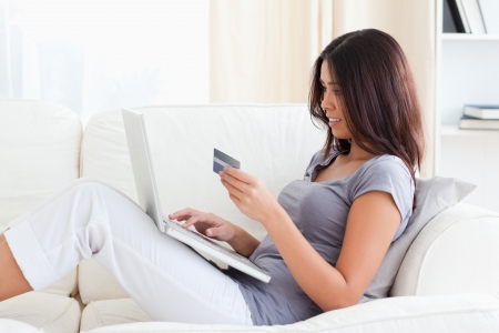 charming woman holding credit card while sitting on sofa in livingroom photo
