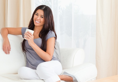 woman with cup looking into camera in livingroom photo