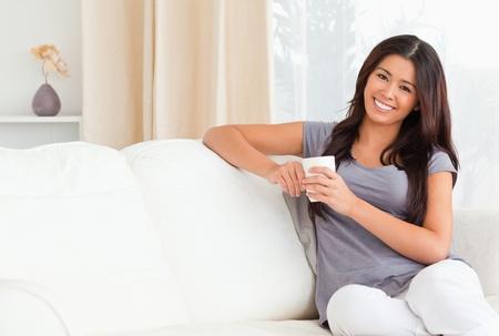 brown leather sofa: donna carina con tazza guardando la telecamera in soggiorno Archivio Fotografico