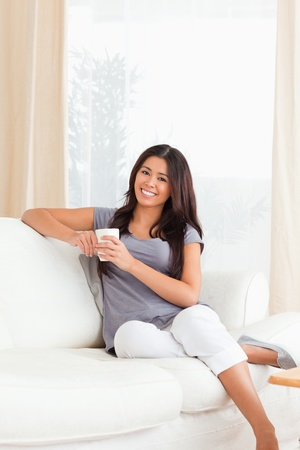 crossleged sitting woman with cup looking into camera in livingroom photo