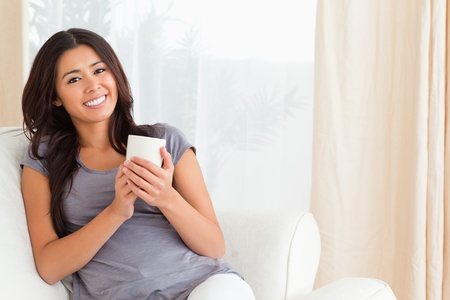 woman holding cup smiling into camera in livingroom photo