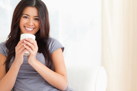smiling woman holding a cup in livingroom photo