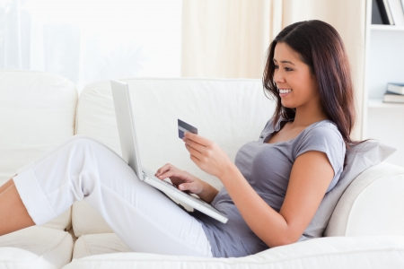 smiling woman sitting on sofa holding a credit card in livingroom photo