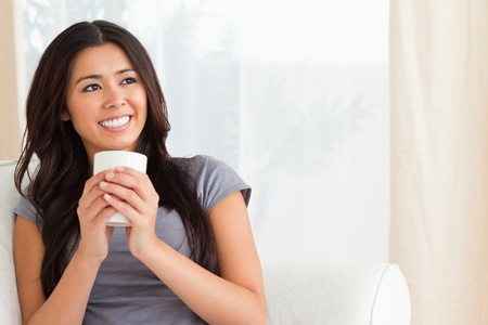 smiling woman holding a cup looking at the ceiling in livingroom photo