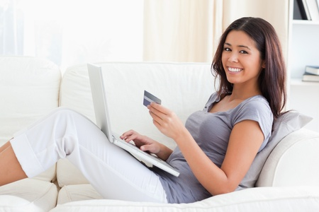 young woman smiling into camera with credit card in hands in livingroom photo