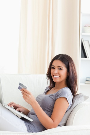 cute woman sitting on sofa in livingroom holding credit card smiles into camera photo