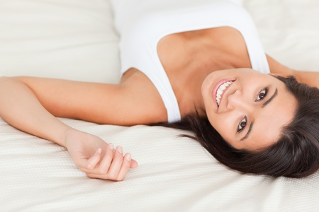 close up of a brunette smiling woman lying on bed in bedroom Stock Photo - 11179107