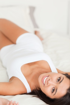 close up of a brunette charming woman lying on bed in bedroom Stock Photo - 11191696