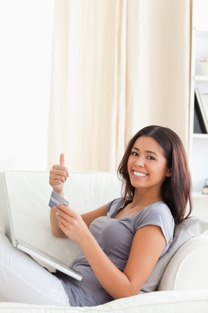 smiling woman with thumb up in livingroom photo