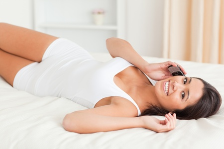 woman lying on bed in bedroom on the phone photo