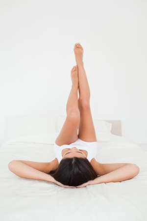 cute woman legs raised up high and arms under her head lying on bed in bedroom photo