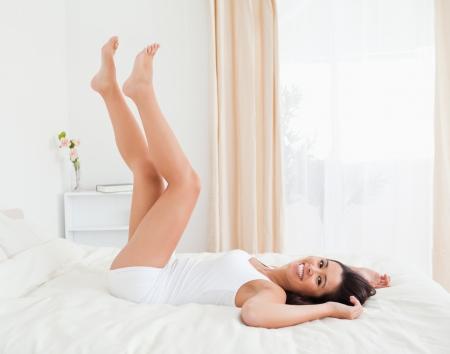 benen: glimlachende vrouw benen omhoog omhoog en de armen onder haar hoofd liggend op bed in de slaapkamer Stockfoto