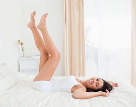 smiling woman legs raised up high and arms under her head lying on bed in bedroom photo