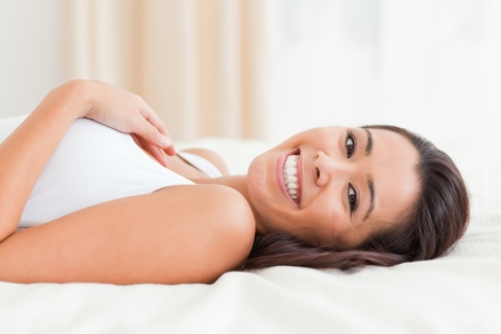 woman lying on bed in bedroom with legs raised  photo
