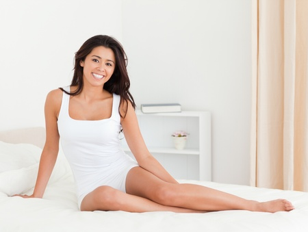 woman sitting on bed in bedroom photo