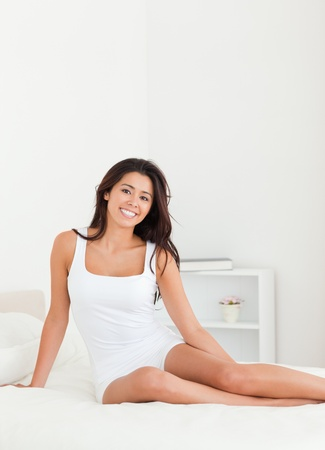 smiling woman sitting on bed in bedroom photo