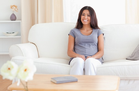 smiling woman sitting on a sofa, there is a table in front of her with a book and flowers on it in the livingroom photo