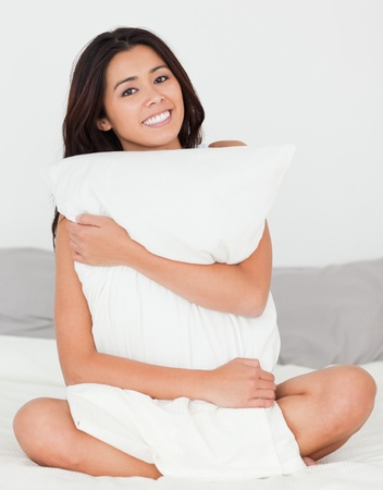 feet in bed: cute woman with pillow sitting on her bed smiling into camera in bedroom