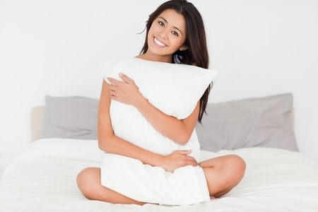 brunette woman with pillow sitting on her bed looking into camera in bedroom photo