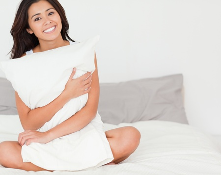 charming woman with pillow sitting on her bed looking into camera in bedroom photo