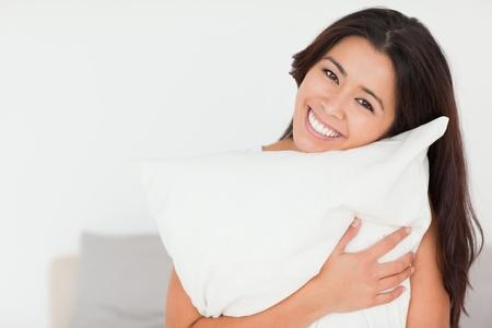 looking into camera: Close up di una donna affascinante con cuscino seduta sul suo letto guardando la telecamera in camera da letto Archivio Fotografico