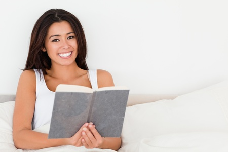charming woman holding book lying in bed looking into camera in bedroom photo